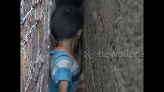 Firefighters free Chinese boy wedged tight between walls - Video