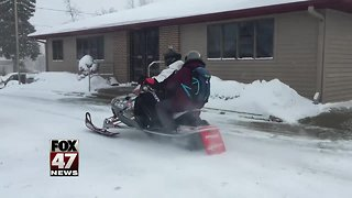 Pharmacists deliver prescriptions on a snowmobile