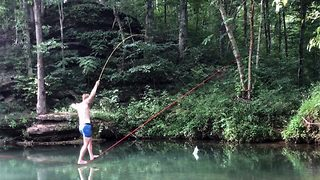 Slackline fishing ends with a splash after student topples into water and loses his catch  - Video