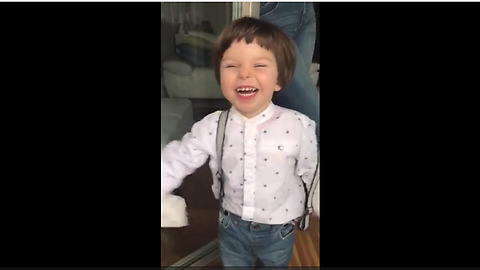 Toddler blows raspberries to help clean the windows
