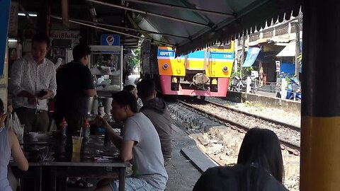 Locals eat at tables just inches from passing trains at Thai restaurant