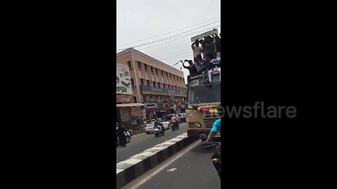 Terrifying moment celebrating students fall from top of moving bus in southern India