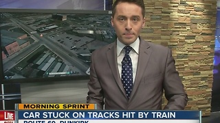 Snow causes driver to get stuck on train tracks, hit by train - Video