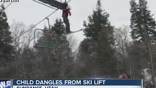 Child dangles from ski lift - Video