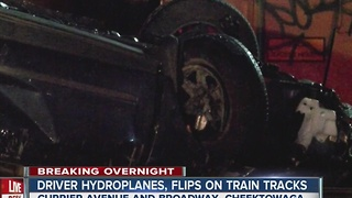 Driver taken to hospital after flipping car on tracks - Video