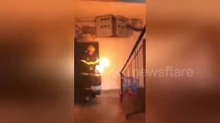 Brave fireman carries flaming gas cylinder out of building - Video