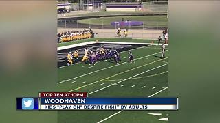 Kids play on in youth football despite fight by adults - Video