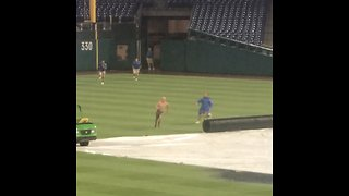 Man runs onto baseball field during ran delay, slides on water-filled tarp