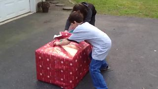"""Three Kids Scream With Excitement When They Open A Christmas Gift"""