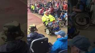 Soccer Fan in Motorized Wheelchair Celebrates Goal - Video