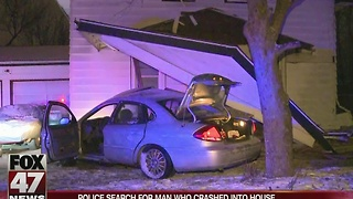 Police search for suspect who crashed into Lansing home - Video