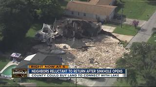 Neighbors reluctant to return after sinkhole opens - Video