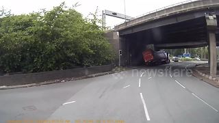 Dashcam captures moment when truck overturns as it passes underneath bridge - Video