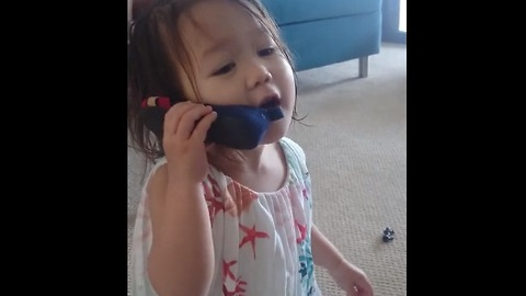 "Toddler on ""cell phone"" is deep in conversation"
