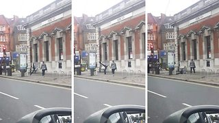 Man performing 'worst John Cleese impression ever' falls over while doing high kicks in London street - Video