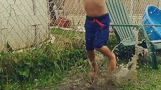 Young Boy Enjoys Jumping In Puddles - Video
