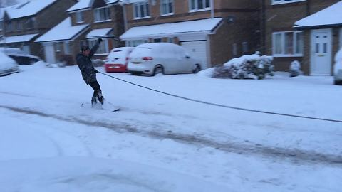 Dude snowboards from back of car through snowy streets