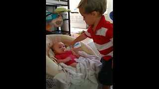 Big brother preciously watches over his baby sister - Video