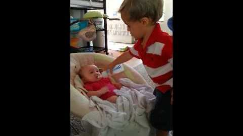 Big brother preciously watches over his baby sister
