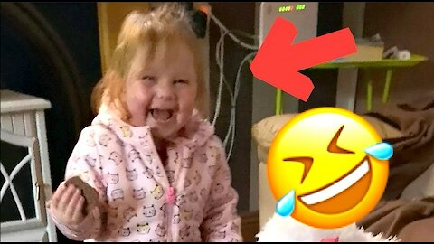 Child laughs hysterically at her toy puppy falling off the table