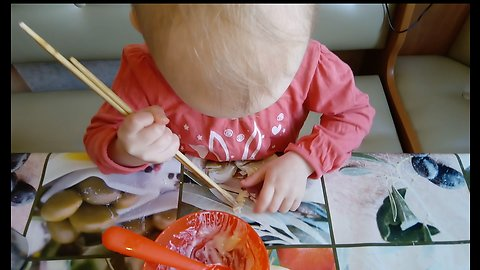 Funny baby trying to learn to eat with chopsticks.