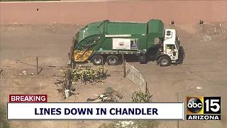 2 trapped after garbage truck hits power pole