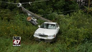 Woman hits gas instead of brake, gets stuck under electric pole