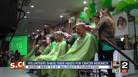 Volunteers shave their heads for childhood cancer research