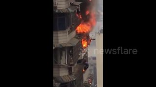 Man hangs out 23rd floor window after escaping from ablaze flat - Video