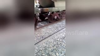 Man escapes miraculously after train runs over him - Video