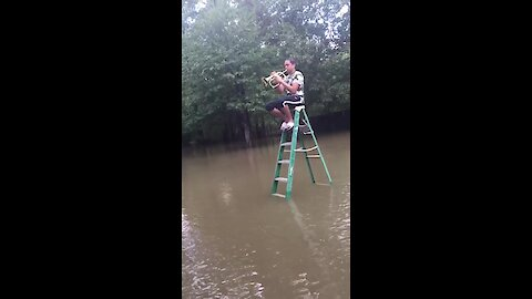 Man plays flugelhorn amidst flooded waters