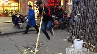 Vendor shows off his kung fu moves while peeling sugarcane