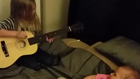 Little girl plays guitar for baby sister