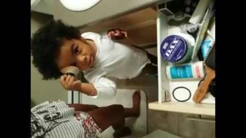 Toddler playing with his mother's makeup brush