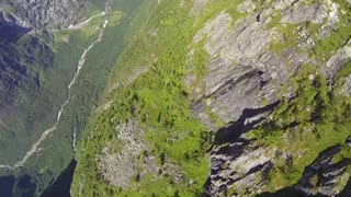 BASE jumper plunges down mountainside rockdrop - Video