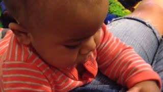 Baby attempts to figure out button on pants - Video