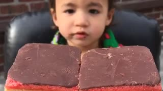 Toddler eating chocolate-topped rainbow cookies