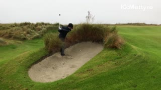 Man in sand hits golf ball falls flips