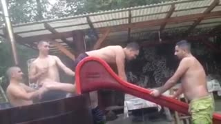 Music shirtless guy sliding down wet slide  - Video