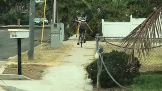 Guy yellow boogie surf board riding down street on unicycle