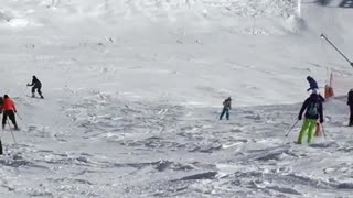 Girl in all black skis down snow slope