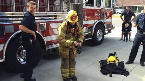 Fireman Demonstrates How He Puts On His Protective Equipment