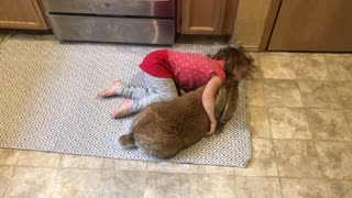 Little Girl Gently Loves on Big Bunny
