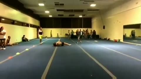 Three girls back flip one in the middle falls