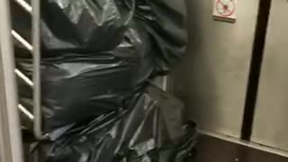 Black trash piled up man in cardboard boxes - Video