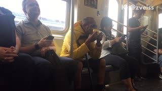 Man yellow jacket eating whole mango subway train