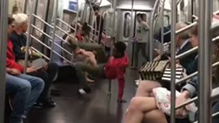 Guy red sweater dancing pole subway needs practice