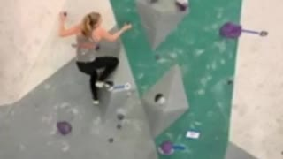 Woman in grey rock climbing indoors falls off