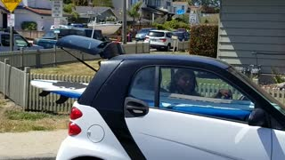 Smart car with surf board in the back of car - Video