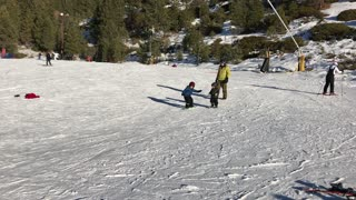 My 5 years old boy snowboarding and his brother running after him
